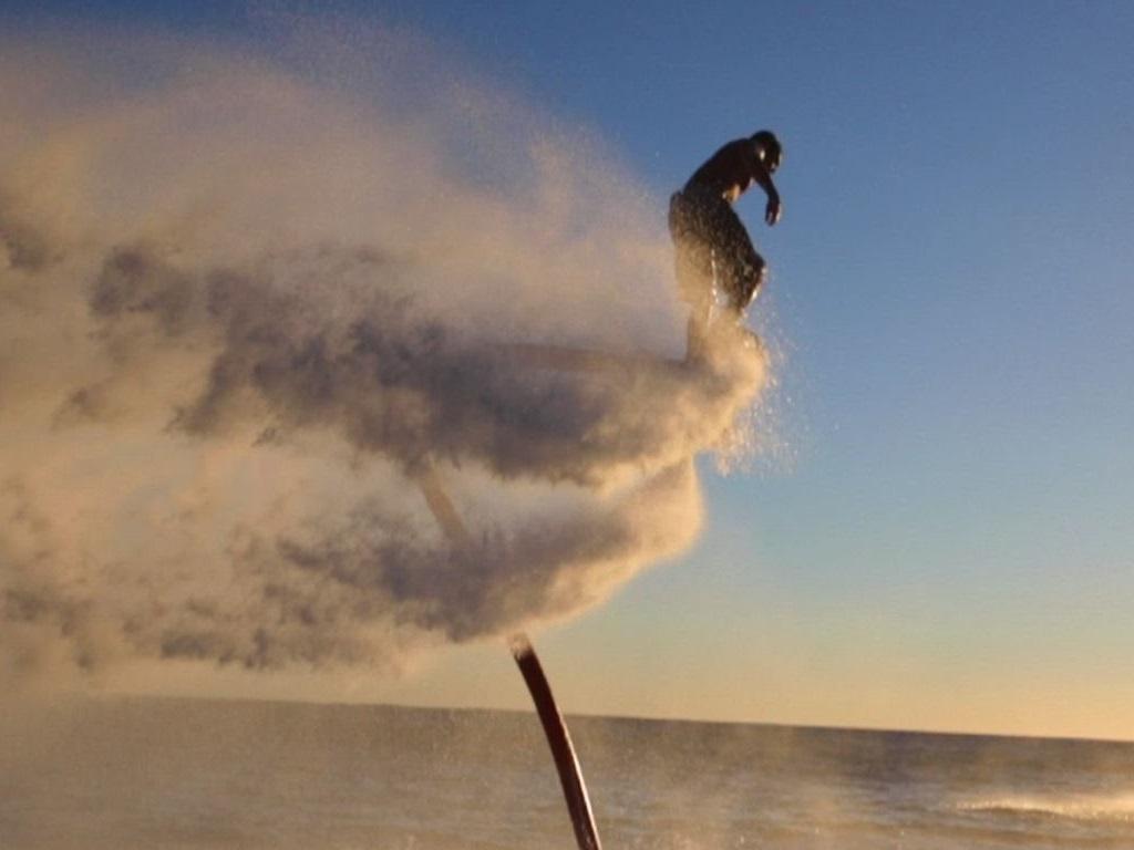 Un flyboardeur laissant une trainée d'eau propulsée lors d'un virage vertigineux.